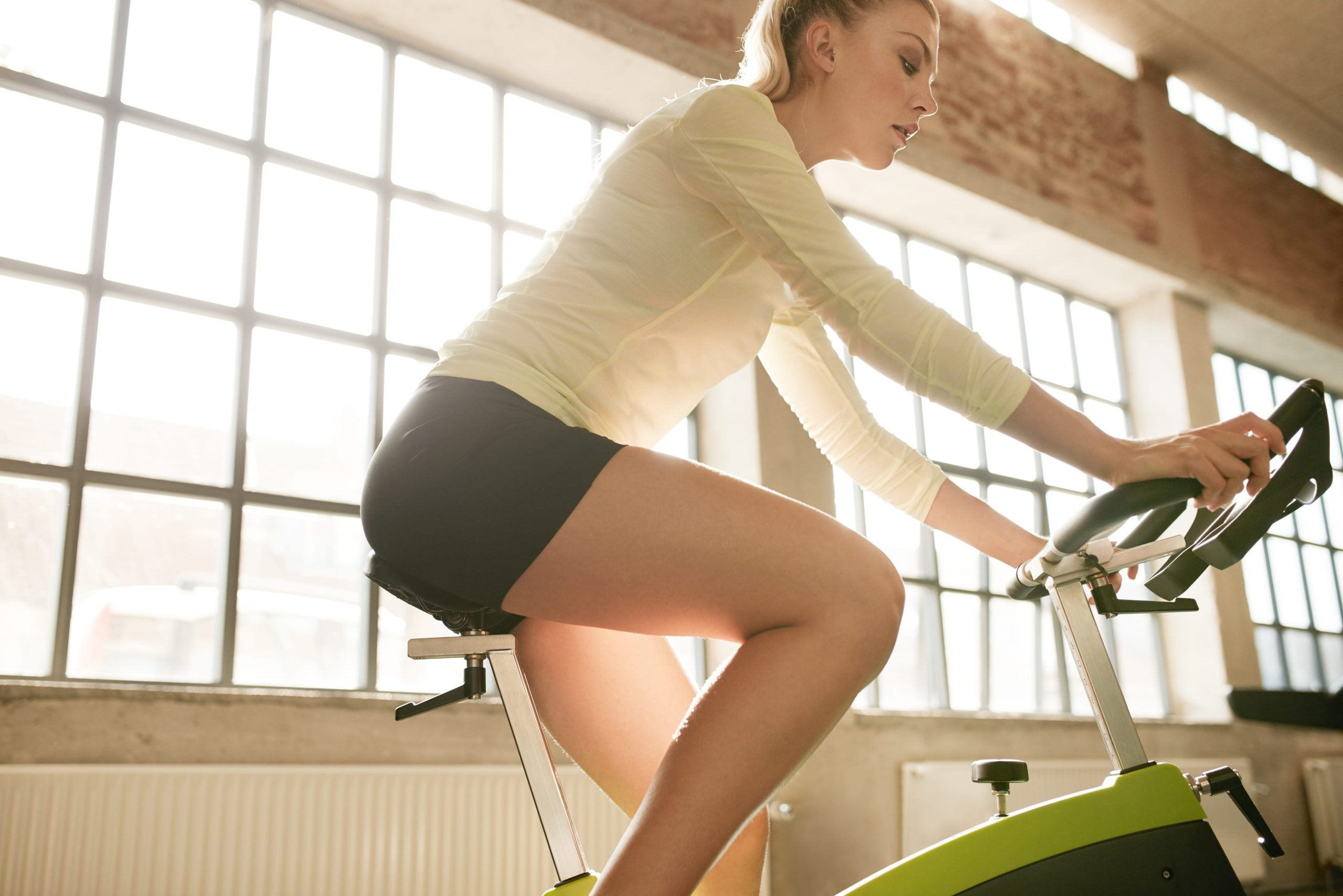 fitness woman on bicycle in gym P66RAPA min 1 scaled