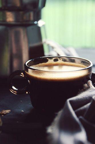 taza pequeña de café negro con una cafeterá italiana al fondo