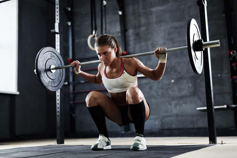 montar un box de crossfit chica en jaula o rack levantando pesas
